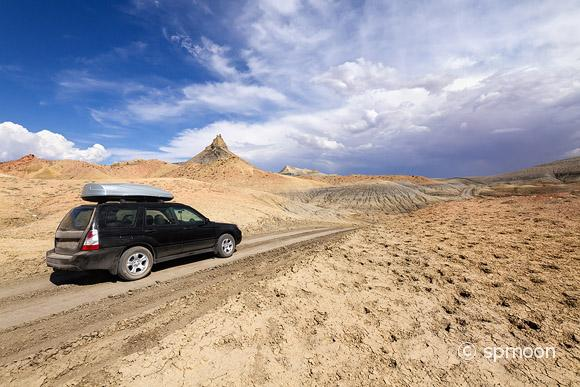 SUV driving on desert dirt road under stormy sky, Lake Powell, Arizona.