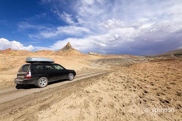 SUV driving on desert dirt road under stormy sky, Lake Powell, Arizona.
