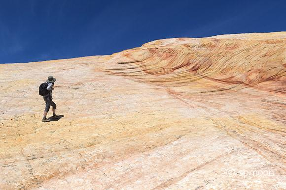 Female Hiker on Yellow Rock - Multicolored sandstone rock on Cottonwood Canyon Road in Grand Staircase-Escalante National Monument, Utah