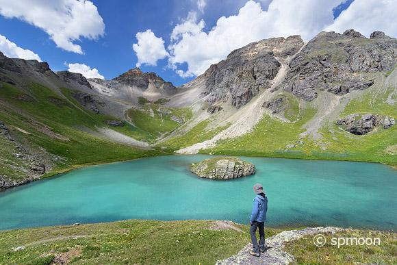 Female hiker looking oever beautiful Island Lake in San Juan Mountains near Silverton, Colorado