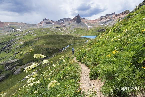 Male hiker waiking on Ice Lake Trail under stormy sky, San Juan Mountains near Silverton, Colorado