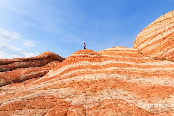 Female hiker walking on top of the striped patterned hill in Yant Flat, Southern Utah.