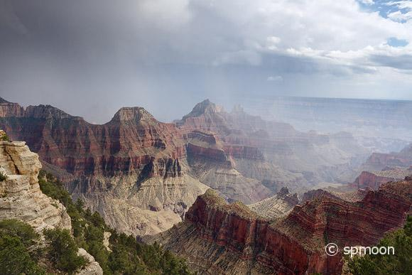 Grand Canyon North Rim under stormy sky.