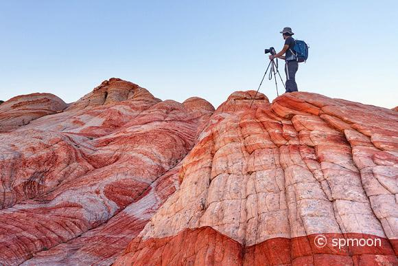 Yant Flat - red, orange, and white striped rock formation in Southern Utah. A male photographer taking picture on top of the colorful hill after sunset.