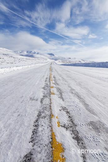 Snow covered winter road in blue sky, Yellowstone National Park, MT.