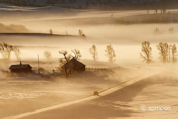 A car driving on snow covered road in foggy winter morning.