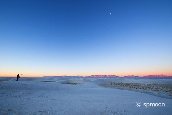 Photographer walking on white sand dunes at dawn, White Sands National Monument, New Mexico
