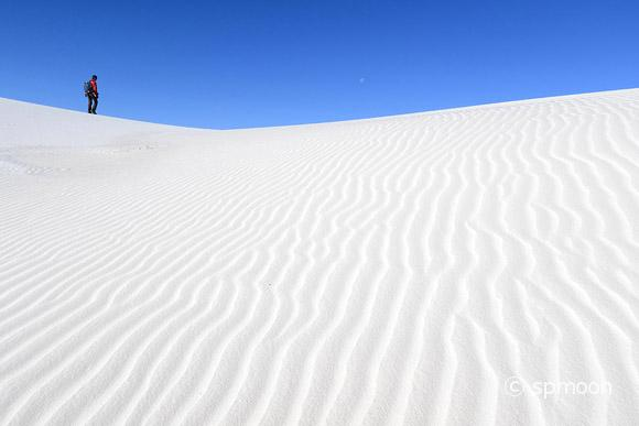 Photographer walking on white sand dunes, White Sands National Monument, New Mexico