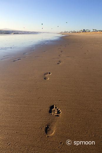 Footprints in the sand at sunset, Huntington beach, CA