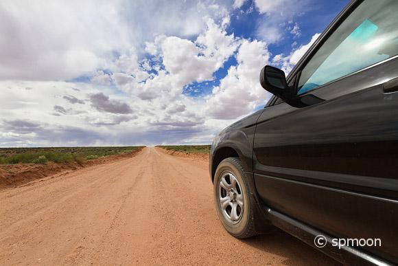 Off road car driving on desert dirt road, Canyonlands National Park, UT