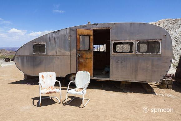 Retro styled camping trailer in desert area.Two old chairs in front.